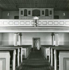 Kirche, Blick zur Orgel (mit Bänken im Kirchenschiff)