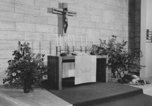 Kirche, Altartisch mit an der Wand hängendem Kruzifix